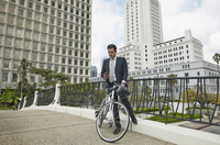 Business man on elevated walkway with bicycle looking at smartphone, Los Angeles City Hall, California, USA