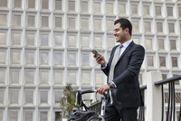 Mid adult business man holding bicycle, looking at smartphone, smiling