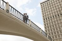 Low angle view of people on footbridge, City Hall East, Los Angeles, California, USA