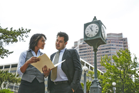 Front view of business people standing next to clock looking at paperwork, waist up
