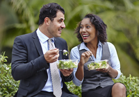 Business people sitting side by side enjoying a salad on lunch break, face to face, smiling