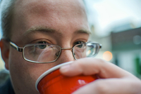 Portrait of young man drinking from takeaway cup on street 11015260336| 写真素材・ストックフォト・画像・イラスト素材|アマナイメージズ