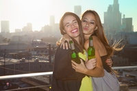 Portrait of two young women hugging at rooftop bar with Los Angeles skyline, USA