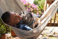 Mid adult man reclining in garden hammock with dog