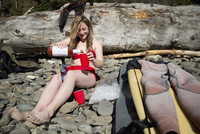 Young woman sitting on rocky beach, pouring drink, Short Sands Beach, Oregon, USA