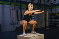 Young woman squatting on gym box with arms reaching out