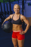 Portrait of young woman training in gym with medicine ball