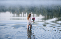 Rear view of young woman wading in misty lake holding bunch of pink roses