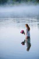 Young woman standing in misty lake holding bunch of pink roses
