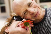 Close up portrait of smiling couple with red flower