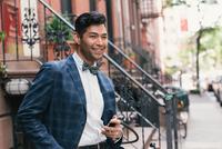 Portrait of stylish businessman with smartphone, West Village, Manhattan, USA