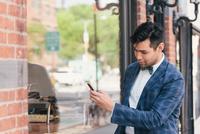 Stylish businessman texting on smartphone, West Village, Manhattan, USA