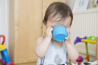 Baby boy drinking from baby cup in playroom