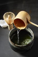 Pouring matcha tea with traditional bamboo tools