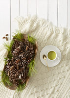Still life with pine cones and needles and cup of matcha tea