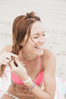 Mid adult woman on beach, plaiting hair