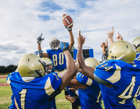 Teenage and young male American football team celebrating victory