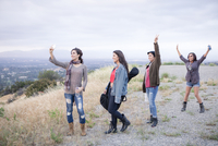 Four adult sisters posing for smartphone selfie on rural hill