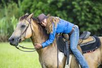Portrait of mature woman, on horseback, hugging horse