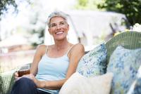 Mature woman relaxing on garden seat