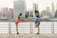 Two friends warming up to exercise together outdoors