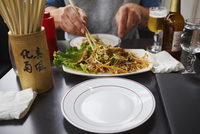 View of person tucking into plate of noodles