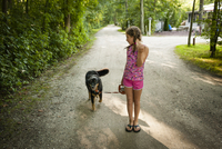 Front view of girl on dirt road, walking dog, looking over shoulder