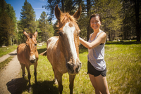 Young woman stroking horse looking at camera smiling, High Sierra National Park, California, USA