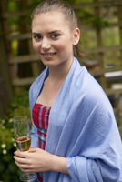 Portrait of teenage girl wearing pashmina, holding champagne flute looking at camera smiling