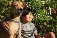 Portrait of boy with arm around dog in garden