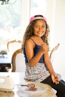 Girl sitting on kitchen counter holding whisk covered in cake mix looking at camera smiling