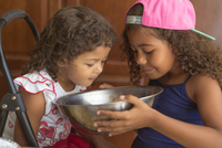 Sisters holding mixing bowl looking down smelling cake mix