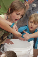 Hand holding sea creature, children looking