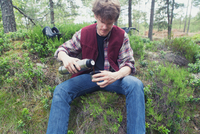 Young man sitting in forest pouring hot drink from drinks flask