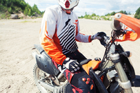 Portrait of young man in motocross clothing, sitting on motorbike, mid section