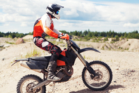 Young man in motocross clothing, riding motorbike