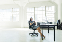 Businesswoman resting on chair by office window