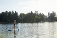 Girl paddling boat in lake, Seattle, Washington, USA