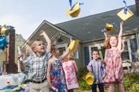 Group of children at kindergarten graduation, throwing paper mortar boards in air