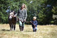 Mother and son walking pony in field