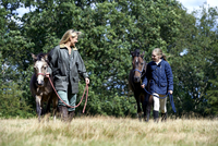 Mother and daughter walking horses in field