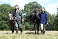 Mother and daughter leading horses in field