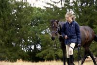 Girl leading horse in field