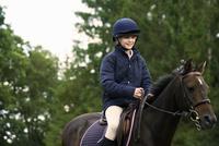 Girl horseback riding in countryside