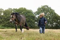 Small boy leading pony in field