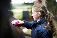 Girl horseback rider grooming horse