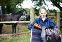 Girl horseback rider carrying saddle