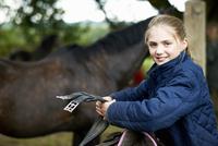 Girl horseback rider preparing saddle