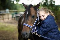 Girl horseback rider hugging horse