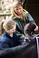 Mature woman and daughter saddling horse